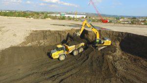 An excavator loading an articulated dump truck.