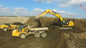 Two articulated dump trucks being loaded by an excavator.