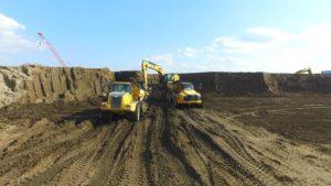 Articulated dump trucks hauling top soil away.