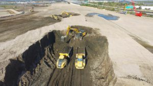An aerial view of two excavators loading dump trucks.