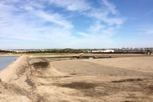 Land being cleared and graded by bulldozers and soil compactors.