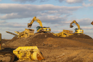 Two excavators loading soil into crushers.