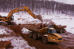 Excavator loading soil and rock into two dump trucks in winter.