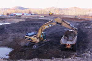 Excavator loading fill into an articulated dump truck.