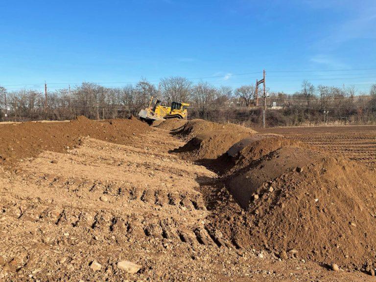 Bulldozer grading piles of soil on a sunny day.