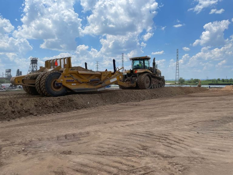 Caterpillar tractor and grader levelling earth at the Hilco Hudson construction project.