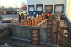 Freshly poured concrete walls with concrete forms being removed.