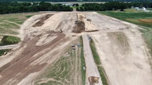 Bulldozers and dump trucks levelling and moving soil.