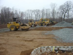 Heavy construction equipment levelling and grading sub-base material in preparation for paving.
