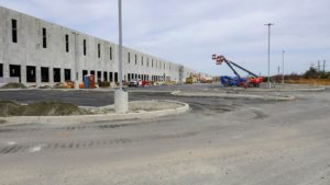 Parking lot construction with concrete curbs and light standards.