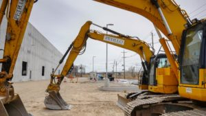 Excavators parked in the surrounding parking lot of the Port E warehouse.