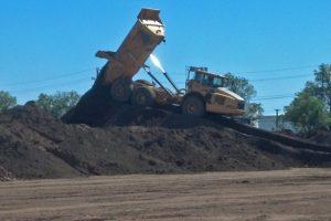 Articulated dump truck unloading top soil.