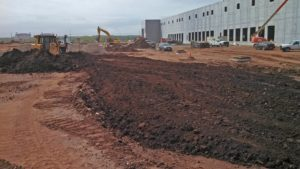 Bulldozer grading soil to level it for the Prologis parking area.