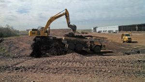Excavator loading articulating dump truck at the Prologis Warehouse project.