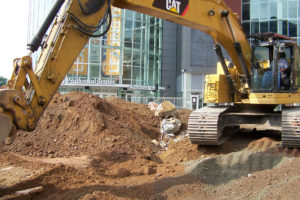 An excavator clearing and levelling the worksite at the Prudential Center.