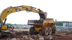 A back hoe loading a dump truck with demolished concrete material.