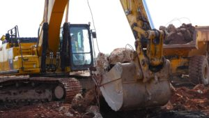 A backhoe clearing demolition site material.
