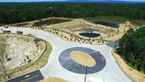 Concrete paved turning circle and stormwater retention ponds at the entrance to the Sailfish warehouse.