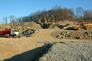 Two excavators clearing and crushing project fill.
