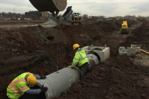Excavator lowering precast concrete pipes for water management and distribution.