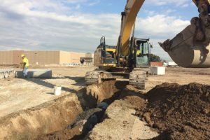 Excavator digging ditches for tiling and drainage.