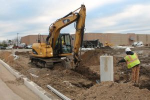 Excavator digging holes for light standard installation.