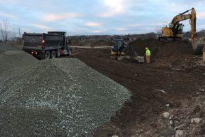 Dump truck unloading sub-base gravel for parking lot grading.