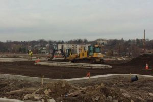 Bulldozer and small excavator grading soil in preparation for sub base.