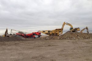 Excavators loading soil and rock materials into a crusher.