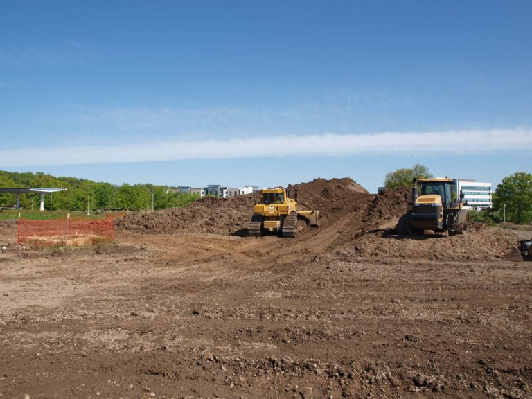 Bulldozer and grader grading and levelling land on a sunny day.