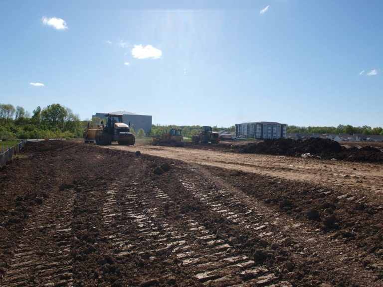 Heavy construction equipment grading and levelling land at The Delaney at the Green construction site.