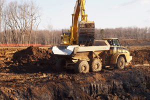 Excavator loading articulation dump truck with soil.