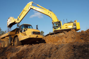 Excavator loading a dump truck with top soil.