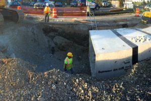 Construction workers placing water management system with backfill