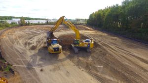 Aerial view of excavator loading soil into a dump truck.
