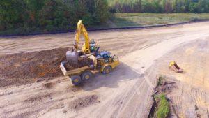 An alternate birds eye view of an excavator loading a dump truck with top soil.