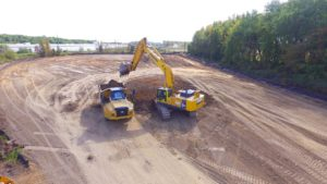 Overhead aerial view of an excavator loading a dump truck with top soil.